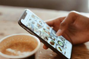 hand holding phone, scrolling through social media